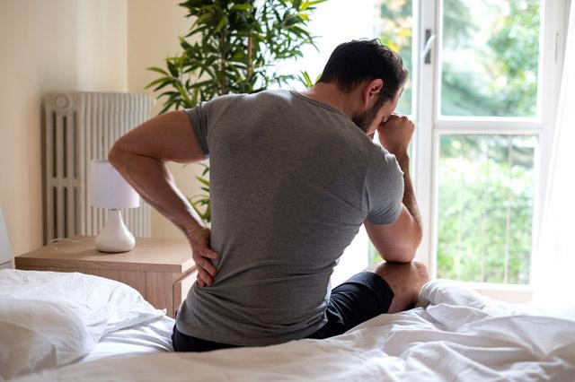 ベッドの上で腰を押さえる男性