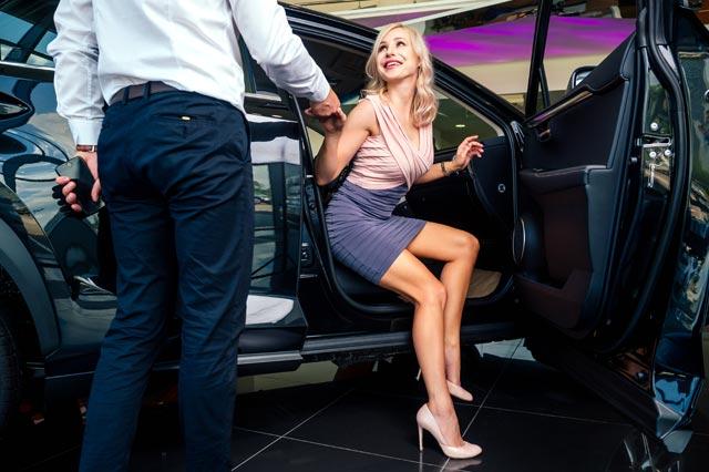 女性が車から降りるのを手助けする男性