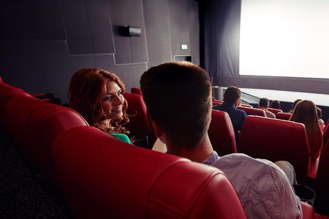 映画館の席に座るカップル