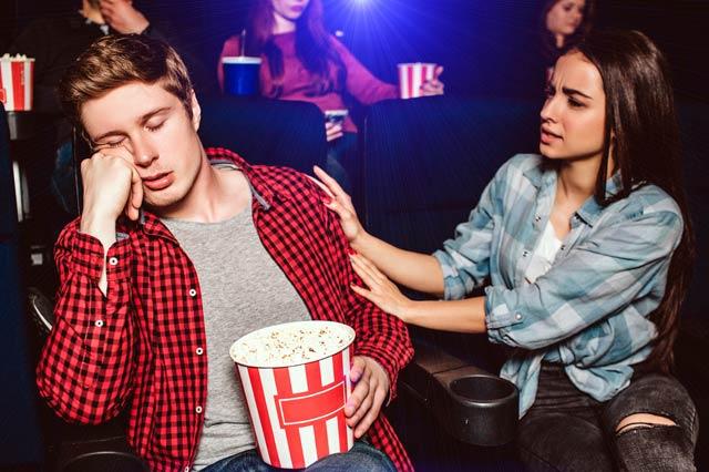 映画館で寝る男性