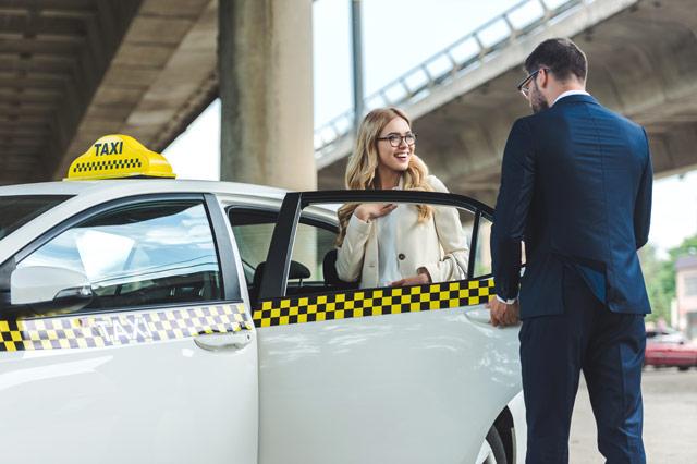女性をタクシーに乗せる男性