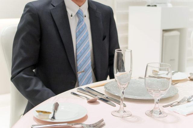 テーブルの下に手を隠す男性