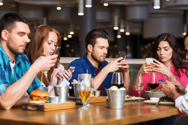 レストランでスマートホンを見る人たち