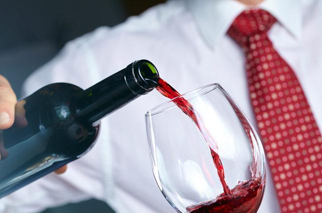 自分のグラスにワインを注ぐ男性