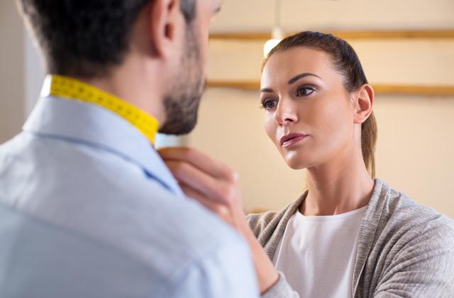 男性の首まわりを測る女性