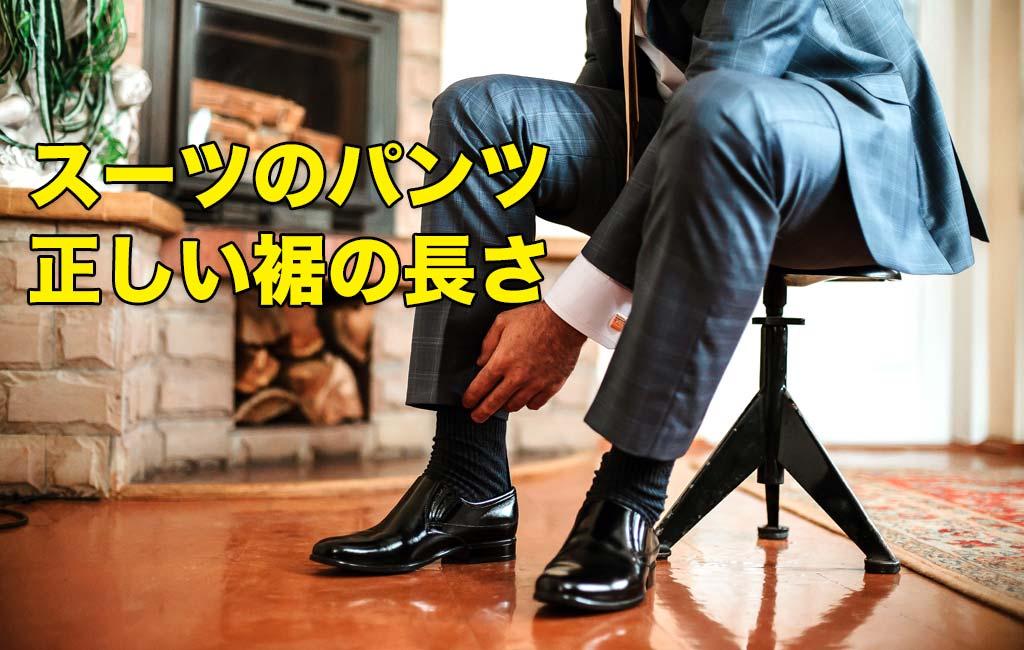スーツのパンツの裾を直す男性