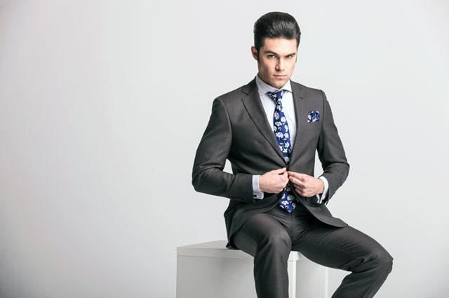 スーツのボタンに手をかける男性