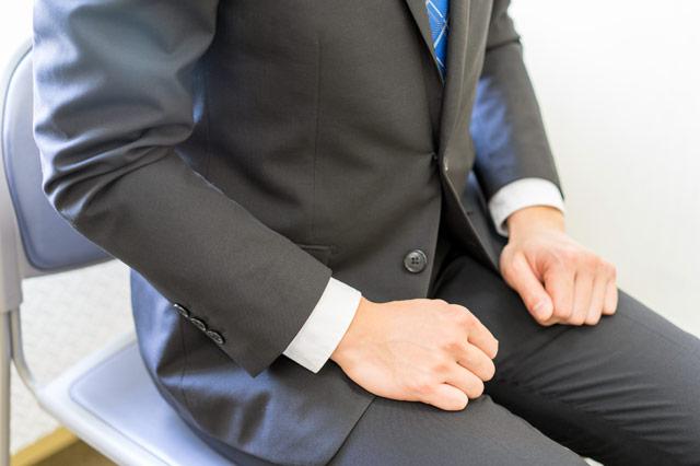 着席しているスーツの男性