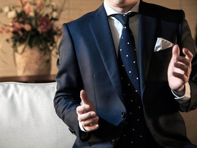スーツのボタンを外して座る男性