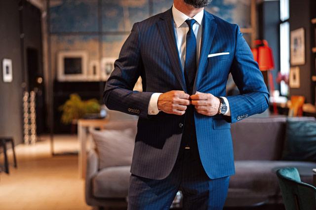 スーツのボタンを留めようとしている男性