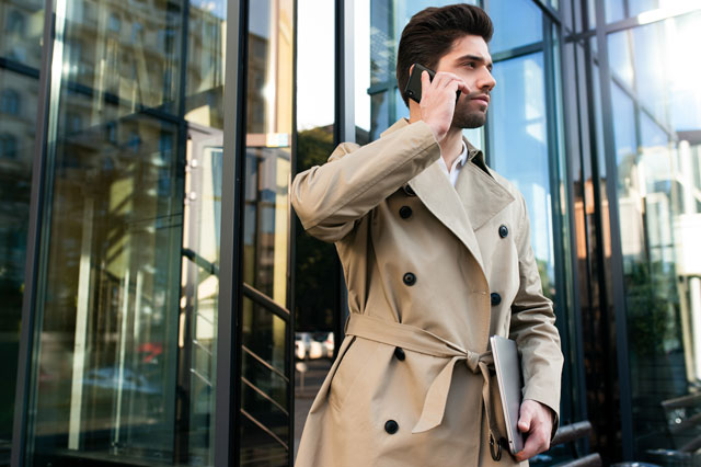 電話をかけるトレンチコートの男性