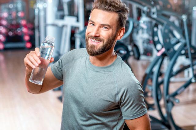 ジムで水を飲む男性